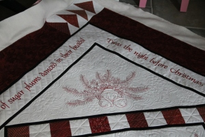 "These corners allow the medallion in the center to placed ""on point"", she then added a skinny charcoal border and then added another machine embroidered border that tells the story of the night before Christmas.  The final finishing border is geese in the corners and a beautiful Christmas print."
