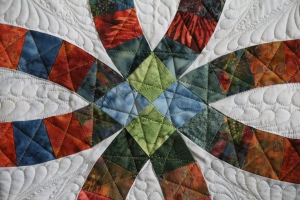 "See there is more quilting in the arcs now.  Can you see the ""star"" I quilted in the blue/green corners?"