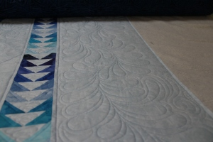 Whimsical longarm style feathers meandering through the border, see the area with background fill and then the area that hasn't been filled yet