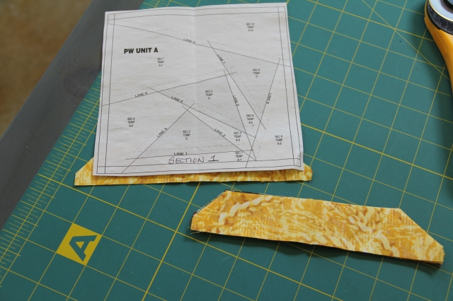 Using a water soluble glue - glue the WRONG side of section 1 to the WRONG side of the paper.  You will see your traced lines to aid you in fabric placement.  (once again pretend this fabric is black!