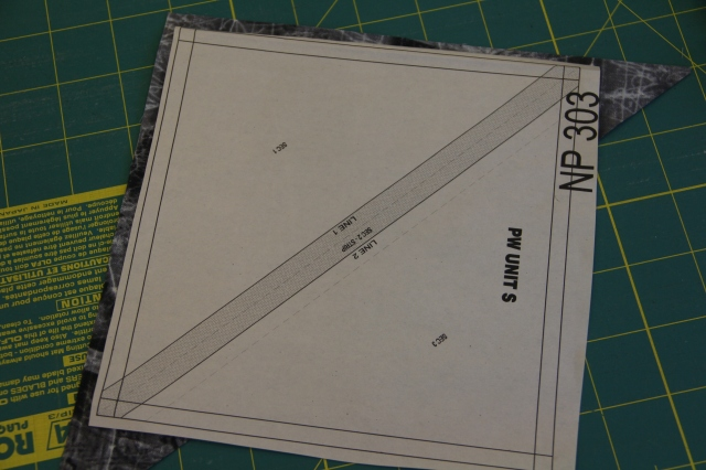 "Take one of your triangles from your 8 1/2"" squares and lightly glue the WRONG side of the fabric to the WRONG side of the paper."