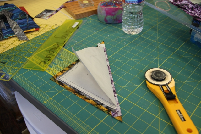 Slide the appropriate color triangle RIGHT side up under the piece you just trimmed (in my example this is the yellow with trees).
